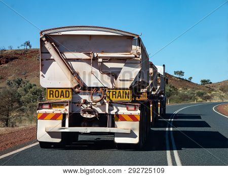 Very long road train truck in Western Australia slowly driving on an asphalt road stock photo