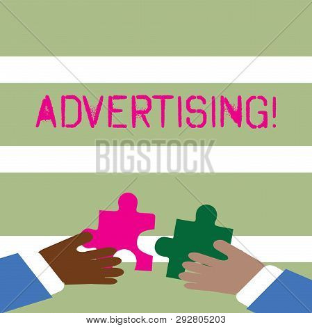 Word writing text Advertising. Business concept for Reach out world branding with digital marketing optimization Two Hands Holding Colorful Jigsaw Puzzle Pieces about to Interlock the Tiles. stock photo