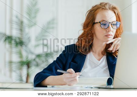 Serious Experienced Female Coach Makes Records In Notepad, Focused At Screen Of Laptop Computer, Has