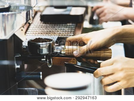 The barista working in a coffee shop, Close up of barista presses ground coffee using the tamper, Barista Make Coffee Portafilter Concept stock photo