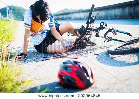 accident clashed on young woman bicyclist in hurt and injured at knee of leg, after accident clashed, with mortal wound and bleeding of blood flow on the surface of street road stock photo