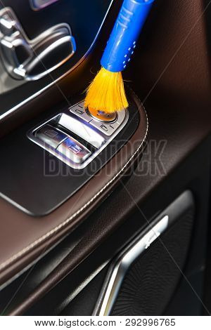 Brush cleaning off dust from the car interior details, control panel of the windows.  A man cleaning car with cloth and brush. Car detailing.  Worker cleaning. Brush and cleaning solution to clean the interior stock photo