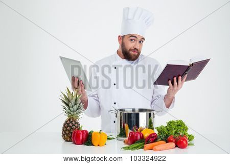 Portrait of a young male chef cook holding tablet computer and receipe book isolated on a white background stock photo