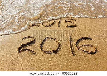 2015 and 2016 year composed on sandy shoreline ocean. Wave washes away 2015.