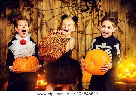 Group of joyful children in halloween costumes posing together in a wooden barn with pumpkins. Halloween concept. stock photo