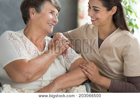 Young nurse in beige uniform and elder lady spending an afternoon together in a retirement home stock photo