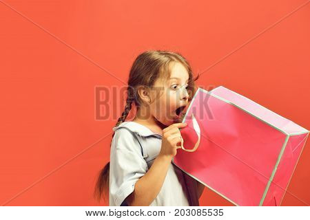 Fashion and shopaholism concept. Girl holds pink shopping bag and looks inside. Kid with surprised face and stylish hairdo does shopping. School girl with package isolated on salmon red background stock photo