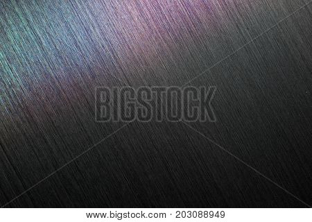 Brushed metal or hairline metal in dim light.  With rainbow sheen or reflection. stock photo