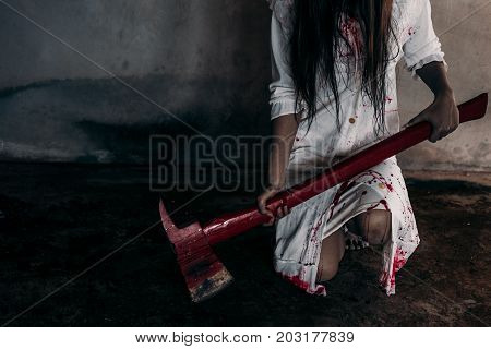 Zombie woman or ghost holding axe sitting with blood in house of ruin nightmare horror of scary fear on hell is monster devil in halloween festival.