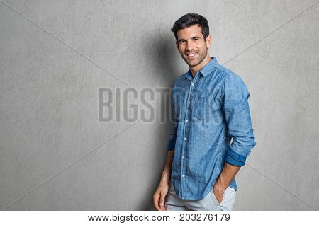 Happy smiling man leaning against grey wall. Portrait of proud mid man isolated on grey background.