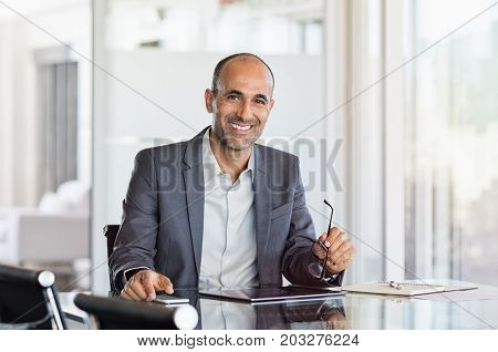 Happy mature business man holding spectacles in modern office. Successful senior businessman sitting