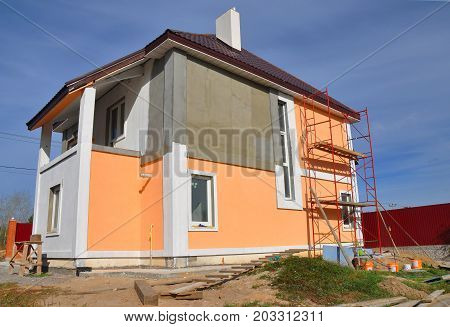 Construction or repair of the rural house with balcon eaves windows chimney roofing fixing facade insulation plastering and using color. House construction. stock photo
