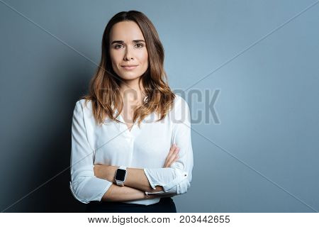 Professional businesswoman. Confident beautiful optimistic businesswoman standing cross armed and looking at you while being ready to work