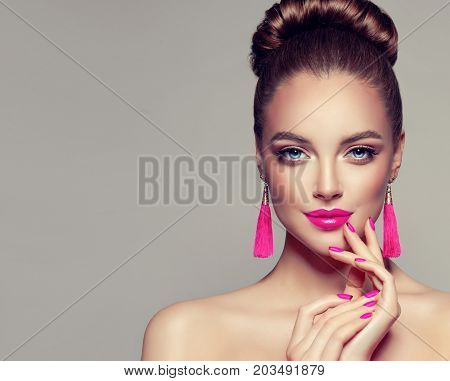 Beautiful model girl with pink fuchsia manicure on nails . Fashion makeup and cosmetics . Large earrings tassels jewelry Magenta color .