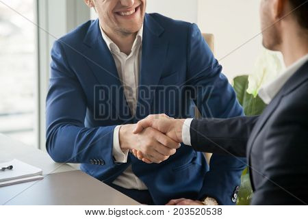 Businessman in blue suit handshaking at business meeting, trying to make positive first impression on partner at negotiation, welcoming new colleague in office. Successful partnership, close up