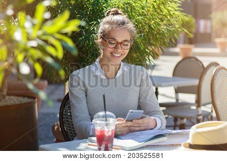 Outdoor Image Of Young Smiling Caucasian Woman Communicating With Boyfriend In Text Messages Or Watc