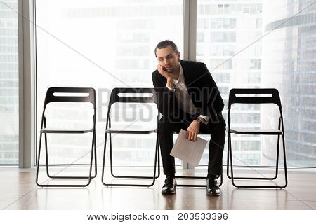 Bored young man in formal suit sitting on office chair in waiting room with document or resume in hand. Young job candidate or businessman waiting too long for interview or business meeting to start. stock photo