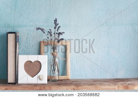 Shabby old interior decor for farmhouse. Lavender in glass vase and blank photo frame on a vintage shelf over pastel wall. Home decoration. stock photo