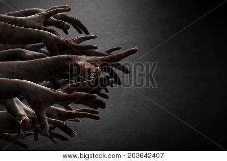 Scary zombie hands reaching in dark room