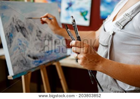 Closeup of young beautiful middle age white Caucasian woman artist drawing painting with acrylic paints on canvas. Female hands holding paintbrushes in art studio. Lifestyle activity hobby concept stock photo