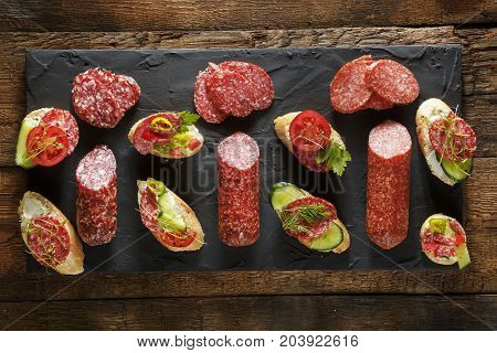 Variety of mini sandwiches and bruschettes with cream cheese vegetables and salami. Sandwiches with cheese cucumber radish tomatoes salami thyme lemon zest on a light background top view. stock photo