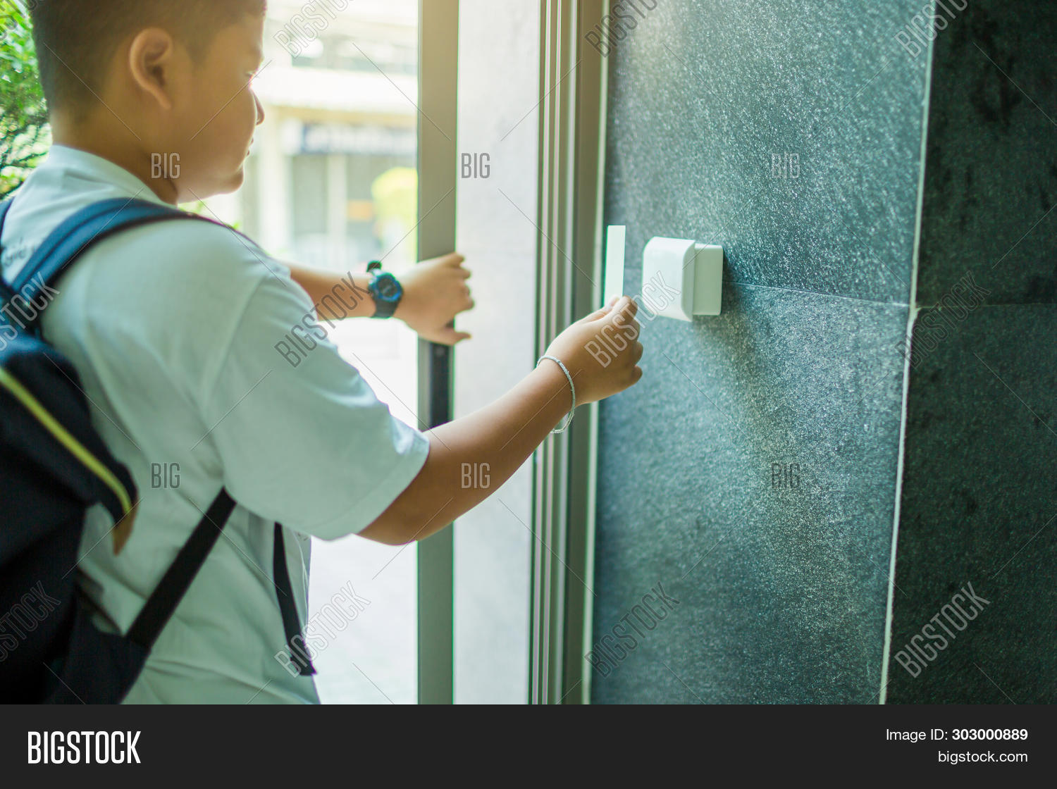Door Access Control. Boy Holding A Key Card To Lock And Unlock Door At Home Or Condominium.