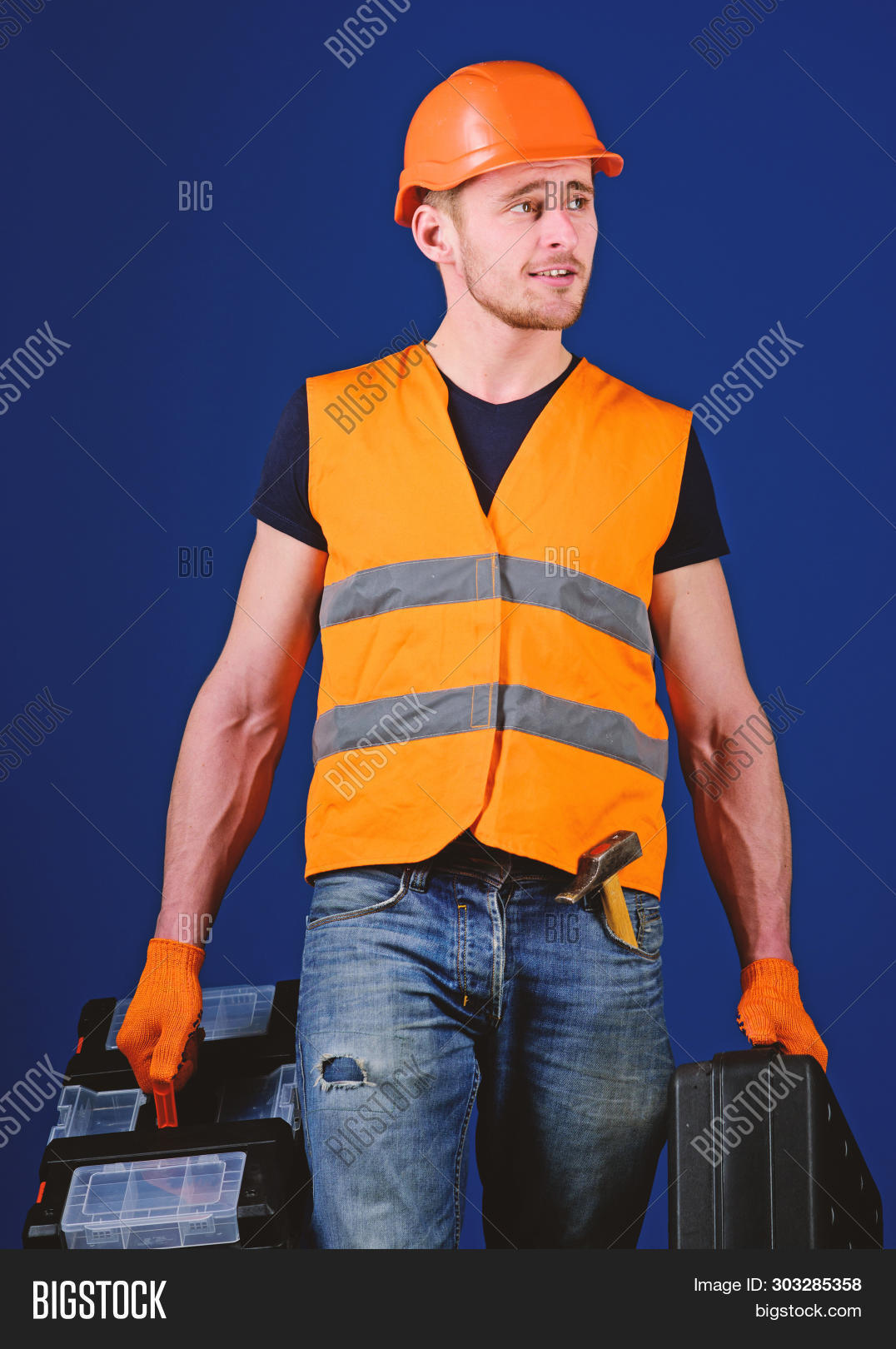 Handyman, Repairman On Dreamy Face Goes And Carries Bags With Professional Equipment. Man In Helmet,