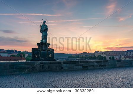Statue of John of Nepomuk on empty Charles bridge in Prague on sunrise stock photo