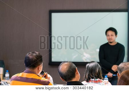 Back side of audience share the idea to Asian Speaker or lecture on the stage in front of the room and everybody in the conference hall or seminar meeting room, business and education concept stock photo