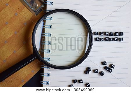 Expert Advice on wooden block and magnifying glass. Motivation concept stock photo