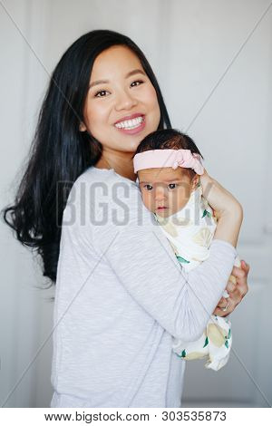 Portrait of beautiful smiling Chinese Asian mother holding cute adorable newborn infant baby girl daughter. Happy family in bedroom. Home lifestyle authentic natural moment. Mothers day. stock photo