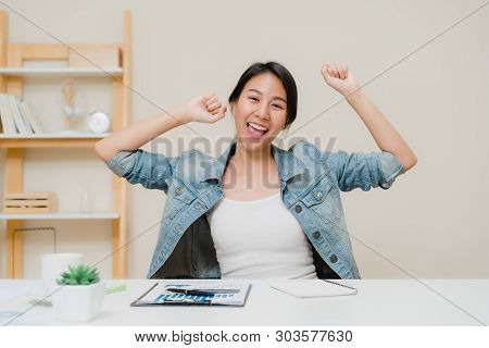 Asia business woman success celebration keeping arms raised at home office. Young asian woman working writing notebook document finance on desk in living room at home. Enjoying time at home concept. stock photo