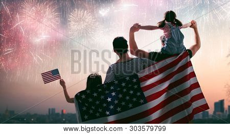 Patriotic holiday. Happy family, parents and daughter child girl with American flag outdoors. USA ce