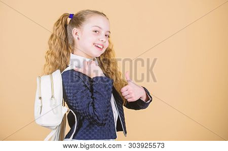 Carrying things in backpack. Learn how fit backpack correctly. Girl little fashionable cutie carry backpack. Popular useful fashion accessory. Schoolgirl ponytails hairstyle with small backpack stock photo