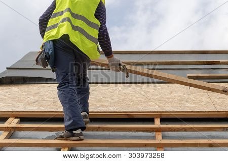 Concept of wood frame work house. Two unrecognizable and professional worker in protective uniform wear standing with plank board or timber in hands on roof top of new modern building construction stock photo