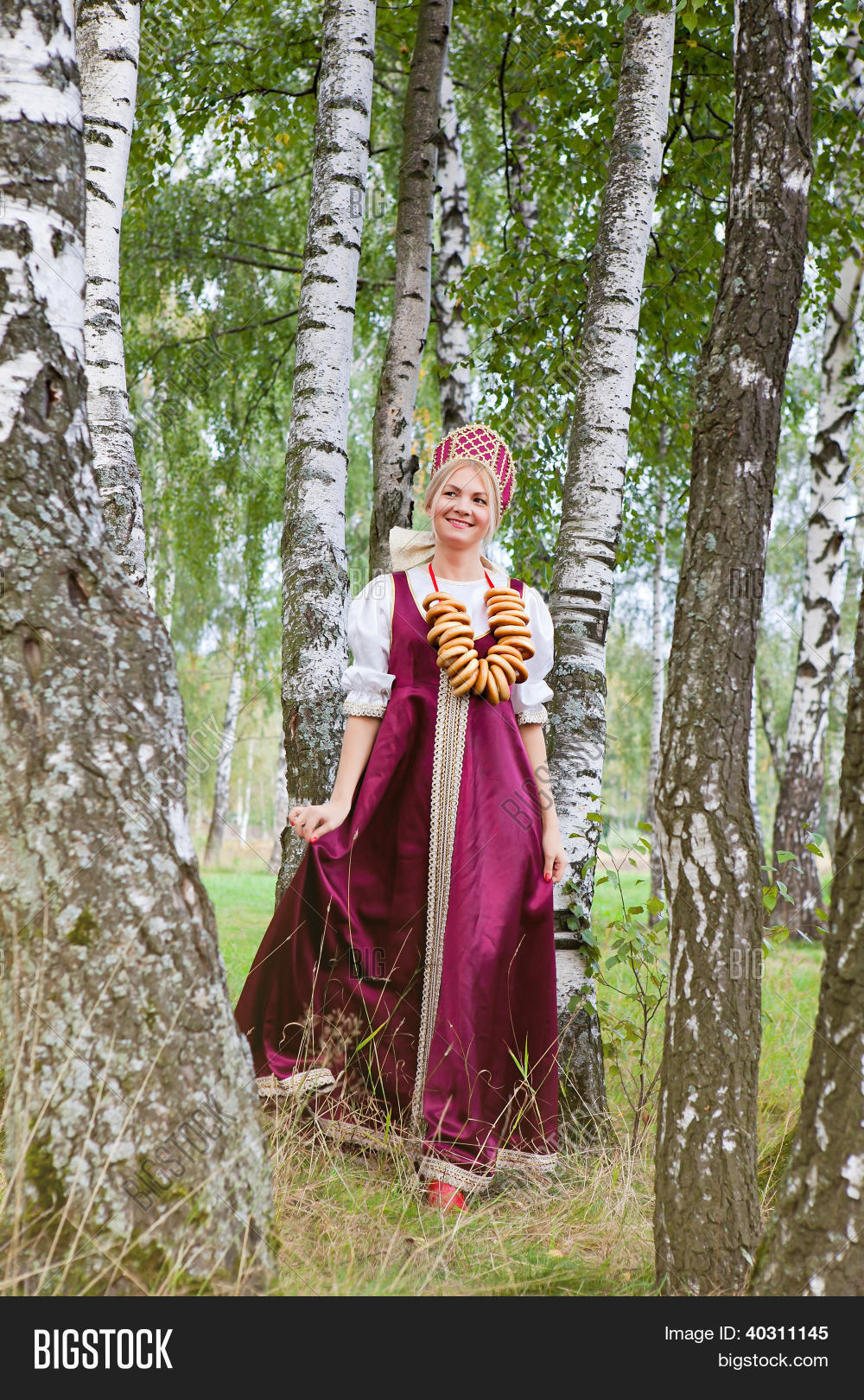 19th,20s,adults,background,beautiful,beauty,birch,bread-ring,caucasian,cheerful,clothing,color,costume,culture,dress,elegance,ethnicity,fashion,female,femininity,forest,garment,girl,happiness,hat,headwear,historical,history,isolated,kokoshnik,old-fashioned,period,person,plait,portrait,red,retro,russia,russian,sarafan,skirt,smiling,standing,style,traditional,wear,woman,years,young
