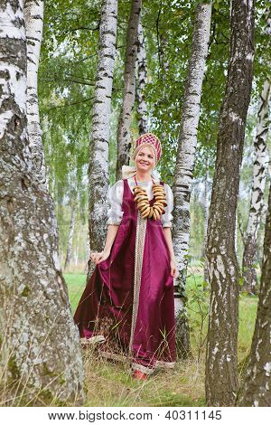 Woman in Russian traditional costume is walking on the forest. stock photo