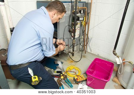 Plumber fixing gas furnace using electric and plumbing tools. Plumber in uniform working on gas furnace. Electric and plumbing tools, electric wire. stock photo