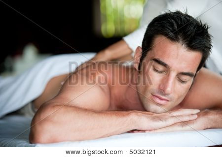 A good-looking man getting a back massage lying down stock photo