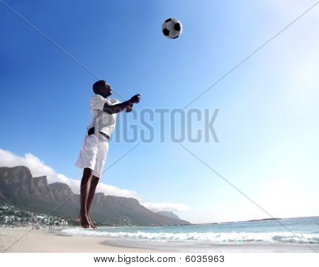 african soccer or football player heading ball on the beach stock photo