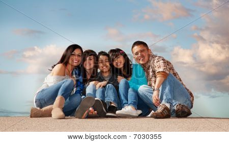 Hispanic family seated against a cloudy sky stock photo