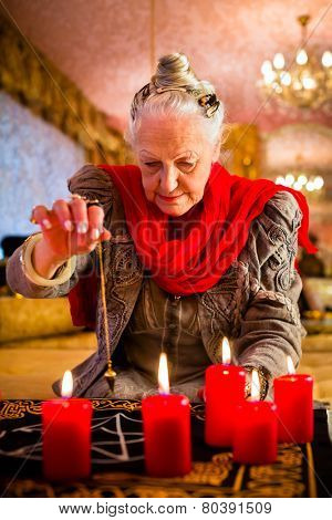 Female Fortuneteller or esoteric Oracle, sees in the future by dowsing her pendulum during a Seance to interpret them and to answer questions stock photo
