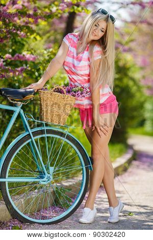 The beautiful blonde of model appearance, with a long straight hair, in dark sun glasses, in in a white-red striped t-shirt without sleeves, poses in park, standing with the blue bicycle, on a luggage carrier of the bicycle there is a wattled basket with stock photo