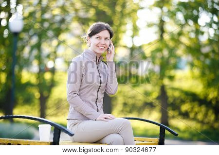 Portrait of happy smiling caucasian woman in park siting on the bench talking on the phone stock photo