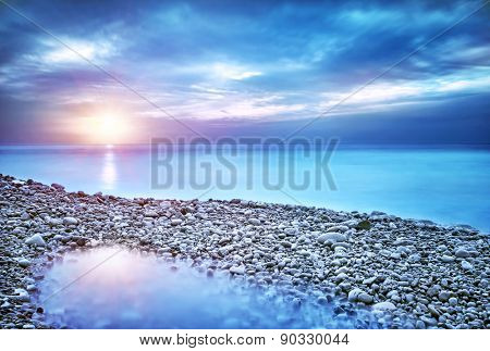 Beautiful seascape, amazing view of pebble coastline in mild sunset light, romantic evening on the b