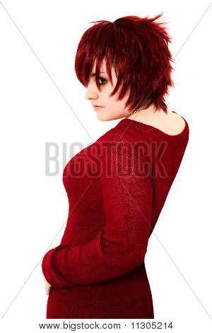 Beautiful 19 year old ginger teenager with shag cut in red dress over white background. stock photo