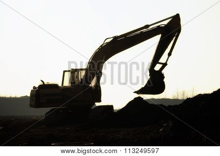Silhouette excavator on construction site, the loading stock photo