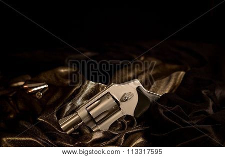 Snubnose 38 revolver laying across gold satin and black velvet with 38 caliber bullets in the background stock photo