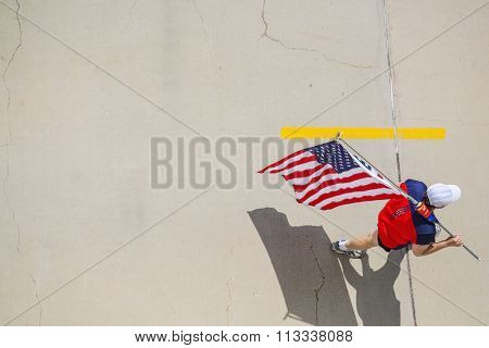 Man walking on cracked cement, carrying an American flag, view from above, focus on hat. stock photo