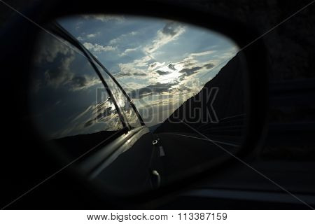Photo closeup of left side outer car rear view retrospection reference mirror on dusk cloudy sky background horizontal picture stock photo